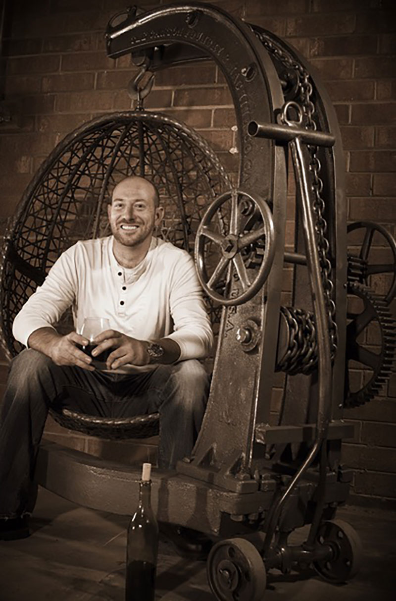 Chris-Lutzweiler-industrial-furniture-maker-sitting-in-his-rustic-hanging-egg-chair-featured