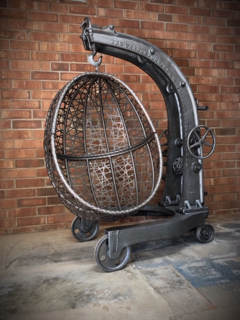Rustic-industrial-hanging-egg-chair-with-antique-crane-stand-by-Chris-Lutzweiler