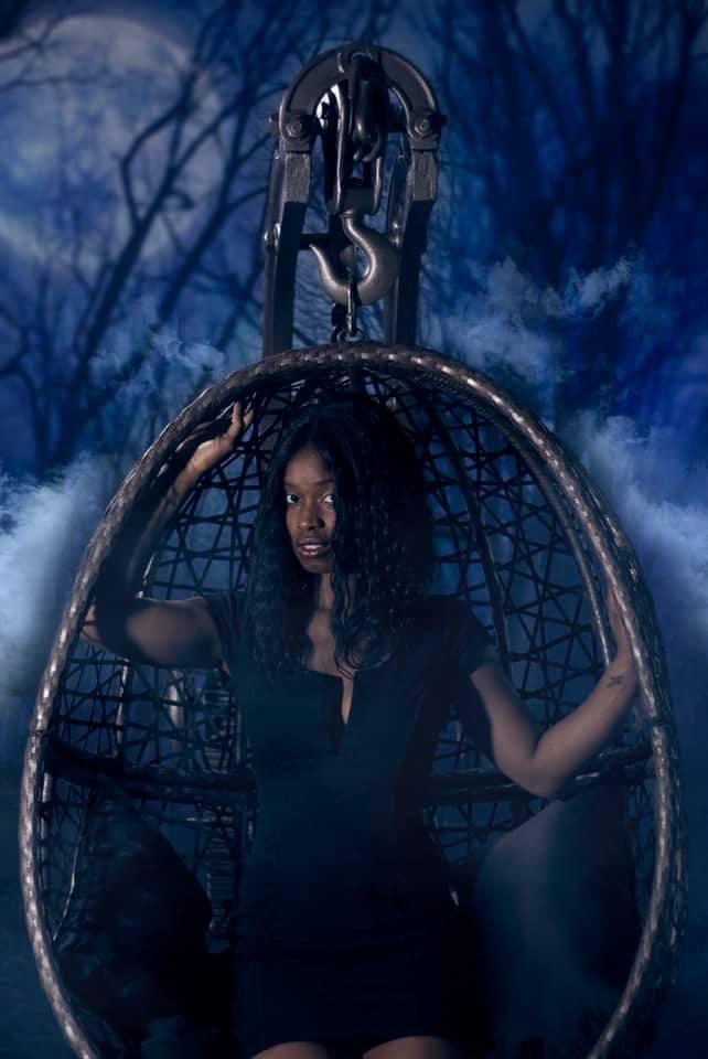 beautiful-black-women-sitting-in-a-rustig-swing-egg-chair