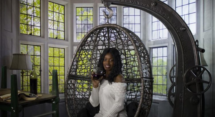 rustic-industrial-designer-hand-made-hanging-egg-chair-a-women-swinging-in-and-drinking-her-wine