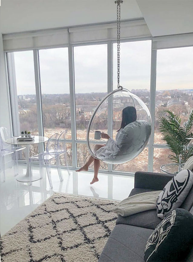a-girl-sitting-in-a-transparent-hanging-ball-chair-bedroom-huge-window-morning-coffee
